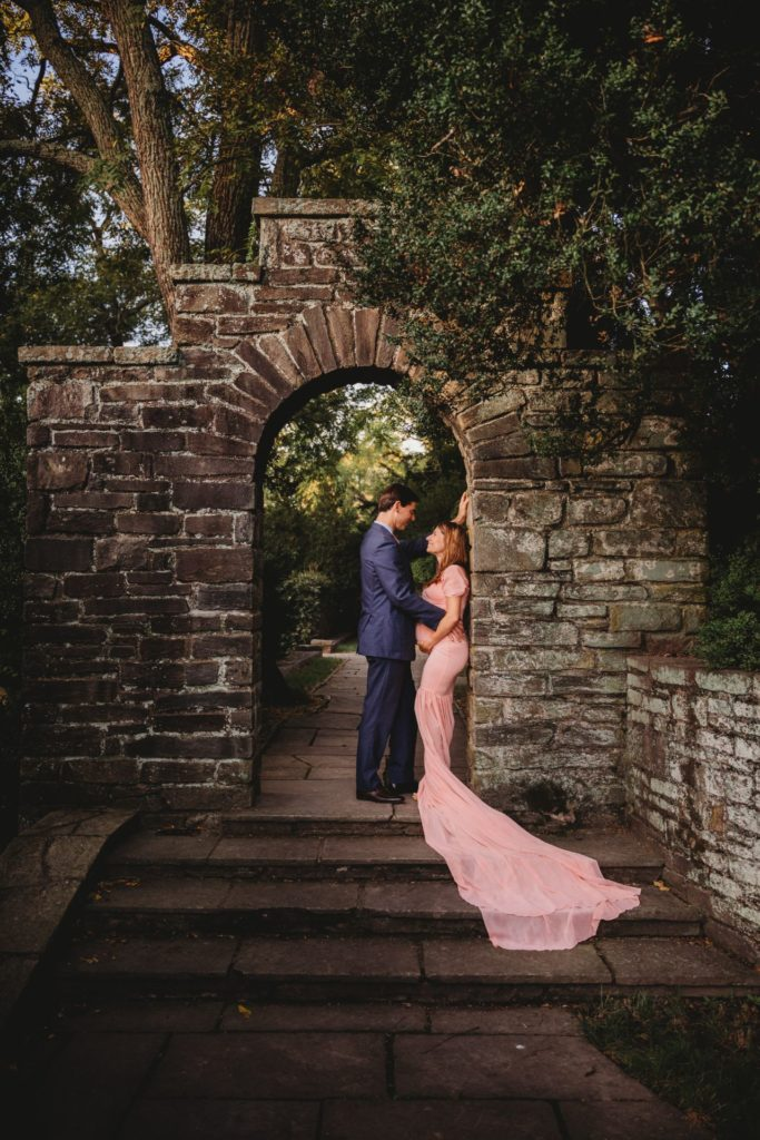Best Maternity and Newborn Photographer Washington DC Maryland Northern Virginia Pregnant Couple leaning on stone arch in formal wear mama to be in pink gown with long train and dad to be in blue suit